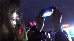 Young girl recording night show video with her mobile phone. 4K shot Stock Footage