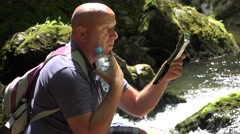 Troubled Tourist Stay Resting  Search a Route on a Map and Drinking Water. Stock Footage