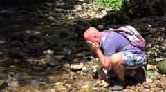 Mountain Tourist Wash His Face with Cold Water and Drink Directly from River. Stock Footage