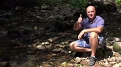 Tourist Standing near a Mountain Creek Showing Thumbs Up in a Adventure Trip.  Arkistovideo