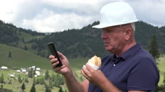 Building Site Worker Take a Rest Use Mobile Phone and Eat a Tasty Sandwich. Stock Footage