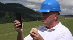 Engineer Taking a Pause Eat a Snack and Access Email Box Using Mobile Phone. Stock Footage