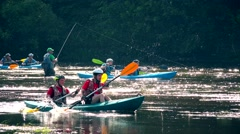 Fisher man fishing and active sportsman people with canoes kayaks on river. Stock Footage