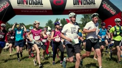 Many young female and male sportsman with orientation maps run at start line. Stock Footage