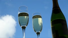 Sparking wine in champagne flutes, time lapse against blue sky with clouds Stock Footage