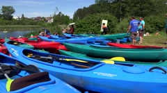 Stack of canoes kayaks on lake shore and competition participants. Stock Footage