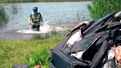Male athlete with helmets and life jackets wade out of water. Stock Footage