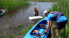 Active people with helmets floating on canoes and foam on lake water. Stock Footage
