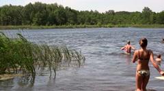 Pretty woman in bikini wade to water and other people recreate on lake beach. Stock Footage