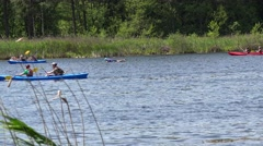 People race with canoes kayaks water sports on wild water river through reeds. Stock Footage