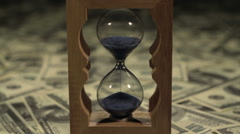 Hourglass standing on american hundred dollar bills. Close-up Stock Footage