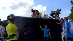 Male athletes helping female woman to climb on wall in sport competition. Stock Footage