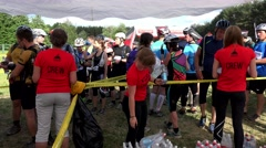 Tired people drink healthy water from plastic bottles after marathon finish Stock Footage