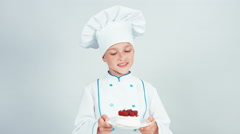 Young baker holds plate with meringue cake and smiling at camera Stock Footage