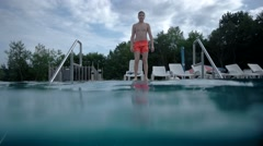 Young Boy Walking Into Swimming Pool and Dive, Underwater Slow Motion Stock Footage