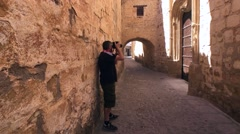 Tourist making photos in Baeza, medieval neighborhood, alleyway with stone arch, Stock Footage