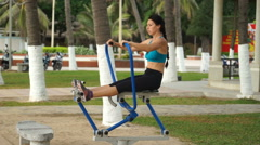Young beautiful woman is doing some sport exercises on rowing machine in the Stock Footage