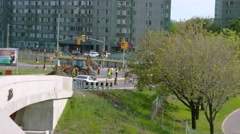 Wide shot- construction workers moving gravel with backhoe Stock Footage