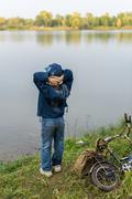 Boy travels with a backpack on the river bank Stock Photos