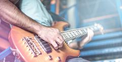 Man plays guitar on stage surrounded by light Stock Photos