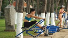 Young athlete woman is doing some sport exercises on rowing machine in the park Stock Footage