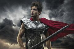Roman Emperor with red cape and armor looking at the horizon before the battl Stock Photos