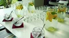 Jug of water with lemon and several empty glasses on the table in restaurant Stock Footage