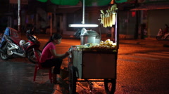 Young asian woman is selling corn on a touristic street at night time in center Stock Footage