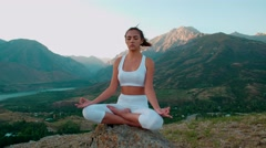 4K beautiful girl in the Lotus position white clothes doing yoga on the Stock Footage
