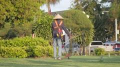 Man cutting grass in Patuxai park,Vientiane,Laos Stock Footage