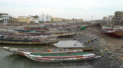 Dirty and poor african cityscape Fishing boats and children in the Senegal river Stock Footage