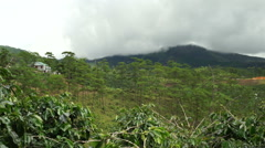House at hill's top in the jungle. Clouds are above high mountains on a Stock Footage