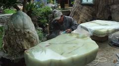 Asian man worker is polishing a granite stone with electric marble in park at Stock Footage