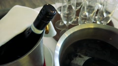 Champagne in bucket with ice ready for serving in restaurant - glasses in backgr Stock Footage