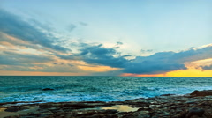 Beautiful clouds over sea and cliffs at sunrise with brilliant colors Stock Footage