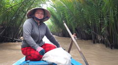 Asian woman is sitting on the nose of a boat which floats muddy vietnamese river Stock Footage