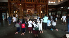 Group of asian women are praying and putting candles in the Buddhist temple at Stock Footage