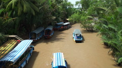 Boats are floating down to a river with muddy water in the vietnamese jungle Stock Footage