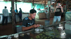 Front view as asian man is packing quickly coconut candies into a wrapper on the Stock Footage