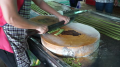 At factory the man knifes big coconut candies on small pieces for sale in Stock Footage