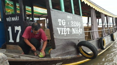 Close-up view where asian man is cutting a coco on the floor of his boat for Stock Footage