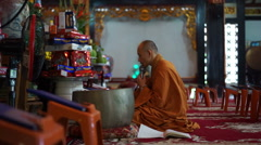 Buddhist monk is sitting on the floor and saying a prayer in microphone into Stock Footage