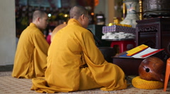 Buddhist monks are sitting in yellow capes a back into the temple and saying Stock Footage