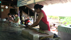 Side view as asian woman is cutting with big knife quickly coconut candies to Stock Footage