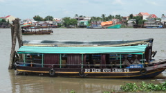 Vietnamese motor ship is parked to a river bank. Another boat floats on the Stock Footage