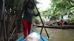 Asian woman is rowing with an oar floating on the muddy water at narrow river in Stock Footage