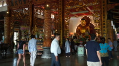 People are walking and praying inside the Buddhist temple. Gold statue Buddha is Stock Footage