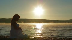 Pregnant Sits On The Lake In The Early Morning And Watch The Sunrise Stock Footage