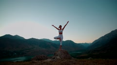 4K beautiful girl in white clothes doing yoga on the beautiful backdrop. Stock Footage