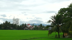 Panoramic view to green field, small houses of local habitants and beautiful Stock Footage